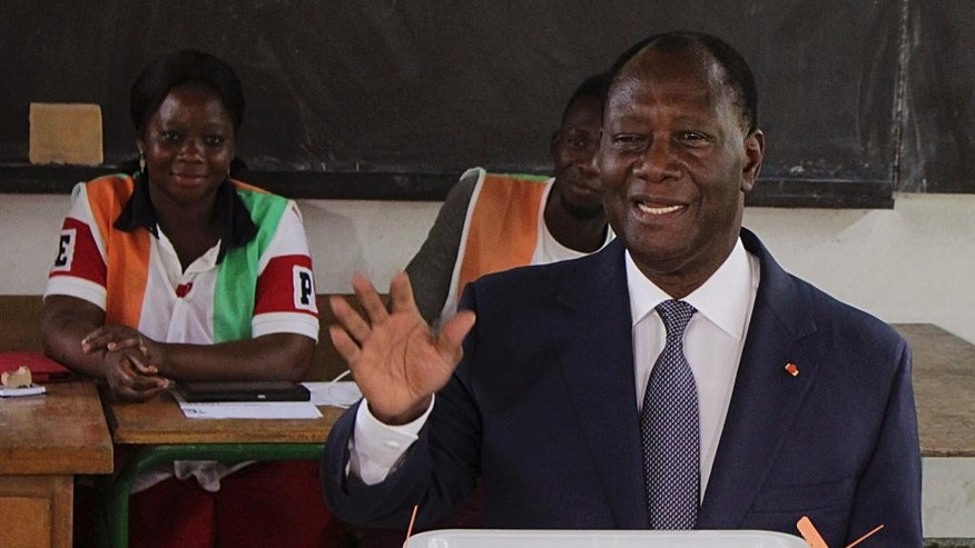 Ivory Coast's President Alassane Ouattara gestures after casting his ballot during Ivory Cost referendum in Abidjan, Ivory Coast, Sunday, Oct. 30, 2016. Voters in Ivory Coast are weighing in on the country's new constitution, which is expected to be approved despite several violent demonstrations by the opposition. The new constitution being considered in Sunday's referendum makes several key changes to the requirements for presidential candidates including the issue of nationality. (AP Photo/Diomande Ble Blonde)
