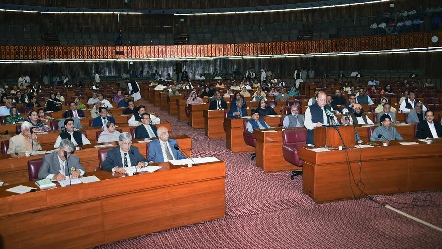 "In this Oct. 5, 2016 photo provided by the Pakistan National Assembly, Prime Minister Nawaz Sharif, standing, addresses the Parliament in Islamabad, Pakistan. A joint session of the Pakistani Parliament approved an anti-honor killing bill this month, by a majority voice vote, that will introduce strict punishment -- a mandatory 25-year sentence for a convicted ""honor"" killer. But the final wording allowed forgiveness of the death sentence. (Pakistan National Assembly via AP)"