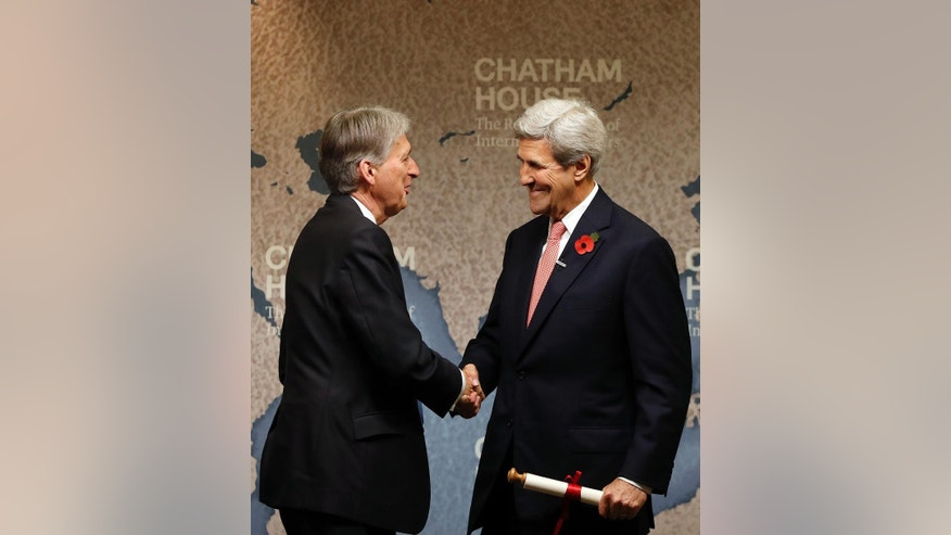 U.S. Secretary of State John Kerry, right, shakes hands with Britain's Chancellor of the Exchequer Philip Hammond,  as he is presented with the Chatham Prize, at The Royal Institute of International Affairs in London, Monday, Oct. 31, 2016. Kerry and Iranian Minister of Foreign Affairs Dr Mohammad Javad Zarif have been voted as the winners of this year's Chatham House Prize. (AP Photo/Kirsty Wigglesworth)