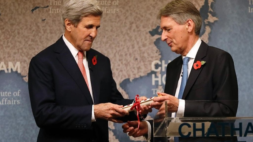 U.S. Secretary of State John Kerry, left, is presented with the Chatham Prize by  Britain's Chancellor of the Exchequer Philip Hammond, at The Royal Institute of International Affairs in London, Monday, Oct. 31, 2016. Kerry and Iranian Minister of Foreign Affairs Dr Mohammad Javad Zarif have been voted as the winners of this year's Chatham House Prize. (AP Photo/Kirsty Wigglesworth)