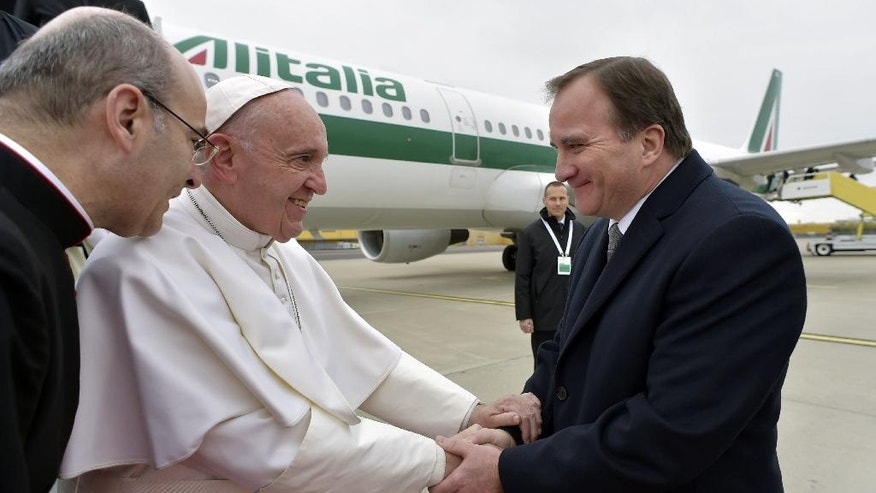 """Pope Francis is welcomed by Swedish Prime Minister Stefan Lofven, right, upon landing at Sturup Airport in Malmo, Sweden, Monday, Oct. 31, 2016. Francis is headed to secular Sweden to mark the 500th anniversary of the Protestant Reformation, a remarkably bold gesture given his very own Jesuit religious order was founded to defend the faith against Martin Luther's """"heretical"""" reforms five centuries ago. (L'Osservatore Romano/Pool Photo via AP)"""