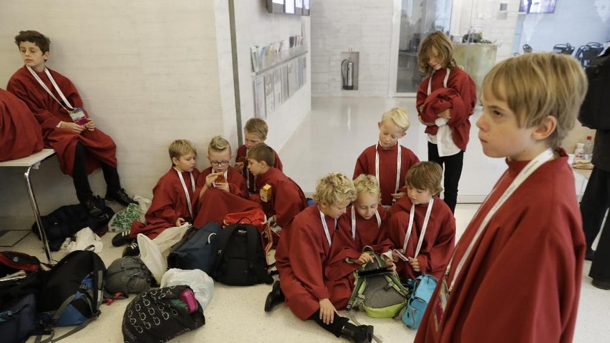"""Altar boys wait for Pope Francis' arrival in a hall room before an ecumenical prayer at Lund's Lutheran Cathedral, in Sweden, Monday, Oct. 31, 2016. Francis traveled to secular Sweden on Monday to mark the 500th anniversary of the Protestant Reformation, a remarkably bold gesture given his very own Jesuit religious order was founded to defend the faith against Martin Luther's """"heretical"""" reforms five centuries ago. (AP Photo/Andrew Medichini)"""