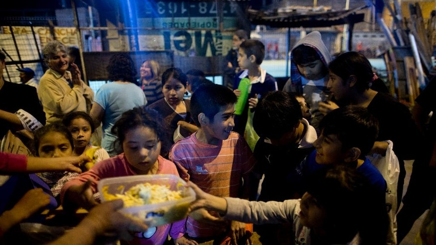 "In this Oct. 13, 2016, children gather for free food given out by Norma Colque at her soup kitchen in the Villa 31 neighborhood of Buenos Aires, Argentina. ""There's food for everyone. Don't worry,"" Colque said as she dumped ravioli into the containers that the families would carry back to their homes. But Colque worries that may not be true for long. (AP Photo/Natacha Pisarenko)"