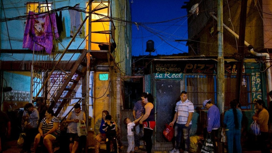 In this Oct. 13, 2016 photo, people line up outside Norma Colque's home to fill their containers with free food to take home to their families, outside the soup kitchen in the Villa 31 neighborhood of Buenos Aires, Argentina. Colque, who gets food from the state to serve about 200 a day, says that in recent months, she has had to stretch the pasta and stew because twice as many people are lining up for food. (AP Photo/Natacha Pisarenko)
