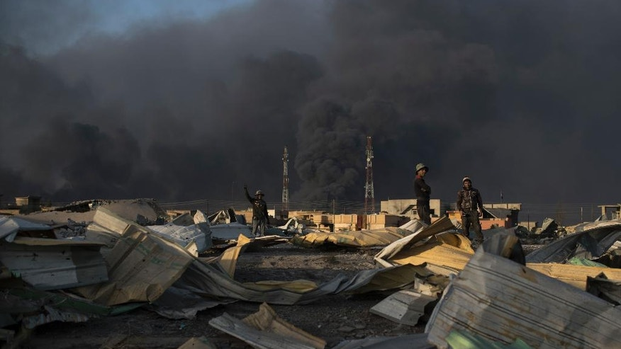 People stand among debris as smoke rises from burning oil fields in Qayara, some 50 kilometers south of Mosul, Iraq, Monday, Oct. 31, 2016. For two weeks, Iraqi forces and their Kurdish allies, Sunni tribesmen and Shiite militias have been converging on Mosul from multiple directions to drive Islamic State militants from Iraq's second largest city. (AP Photo/Felipe Dana)