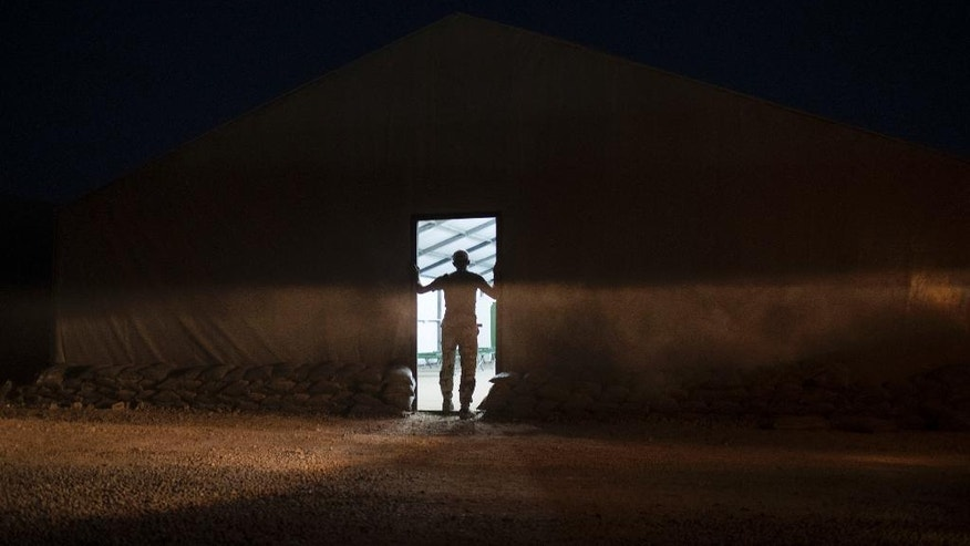 An Iraqi army soldier stands at the entrance of a tent at the Qayara air base, south of Mosul, Iraq, Monday, Oct. 31, 2016. For two weeks, Iraqi forces and their Kurdish allies, Sunni tribesmen and Shiite militias have been converging on Mosul from multiple directions to drive Islamic State militants from Iraq's second largest city. (AP Photo/Felipe Dana)