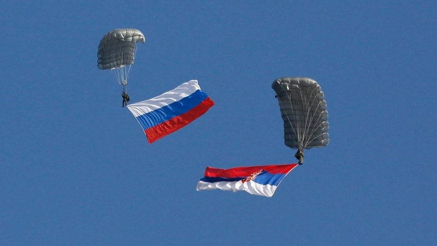 FILE - In this Nov. 14, 2014 file photo, Serbian soldiers parachute from a Mil Mi-8 transport helicopter with a Russian, left, and Serbian flags during the Russian-Serbian joint anti terrorist exercise Srem 2014, at Nikinci training ground, 60 kilometers west of Belgrade, Serbia. NATO is holding an emergency exercise drill in Montenegro while Russia's troops will participate in a war game in Serbia as the two Balkans neighbors that seem to be heading different directions strategically.(AP Photo/Darko Vojinovic, File)