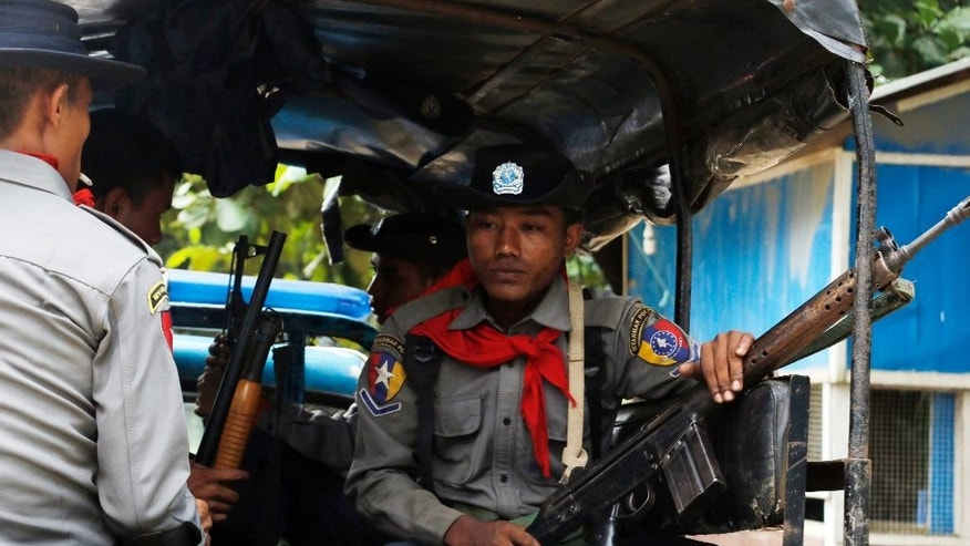 "In this Thursday, Oct. 13, 2016 photo, Myanmar police officers sit in a truck as they provide security in Maungdaw, Rakhine State, Myanmar, a border town with Bangladesh. Just five months after her party took power, Myanmar's Nobel Peace Prize-winning leader, Aung San Suu Kyi, is facing international pressure over recent reports that soldiers have been killing, raping and burning homes of the country's long-persecuted Rohingya Muslims. The U.S. State Department joined activist and aid groups in raising concerns about new reports of rape and murder, while satellite imagery released Monday, Oct. 31, by Human Rights Watch shows that at least three villages in the western state of Rakhine have been burned. Myanmar government officials deny the reports of attacks, and presidential spokesman Zaw Htay said Monday that United Nations representatives should visit ""and see the actual situation in that region."" (AP Photo/Thein Zaw)"