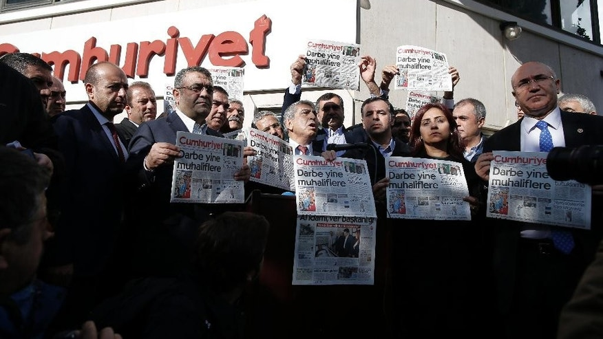 "Journalists and lawmakers hold a latest copy of Cumhuriyet newspaper outside its Istanbul headquarters after police detained chief editor Murat Sabuncu and two columnists of Turkey's opposition Cumhuriyet newspaper and had warrants to detain 10 other senior staff members, in Istanbul, Monday, Oct. 31, 2016, the state-run-Anadolu Agency reported, amid growing fears over Turkey's widening crackdown on dissenting voices. Cumhuriyet's headline reads: ""The coup against opposition again."" (AP Photo/Emrah Gurel)"