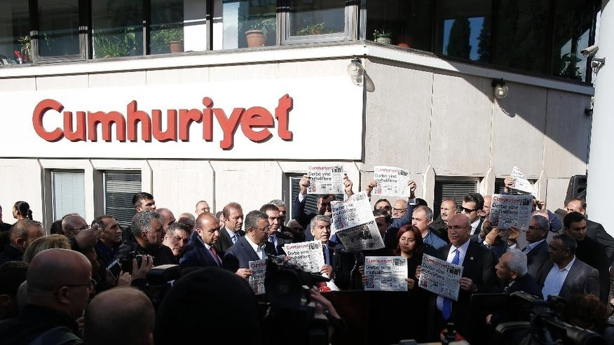 "Journalists and lawmakers hold copies of the latest Cumhuriyet newspaper outside its Istanbul headquarters after police detained chief editor Murat Sabuncu and two columnists of Turkey's opposition Cumhuriyet and had warrants to detain 10 other senior staff members, in Istanbul, Monday, Oct. 31, 2016, the state-run-Anadolu Agency reported, amid growing fears over Turkey's widening crackdown on dissenting voices. Cumhuriyet's headline reads: ""The coup against opposition again."" (AP Photo/Emrah Gurel)"