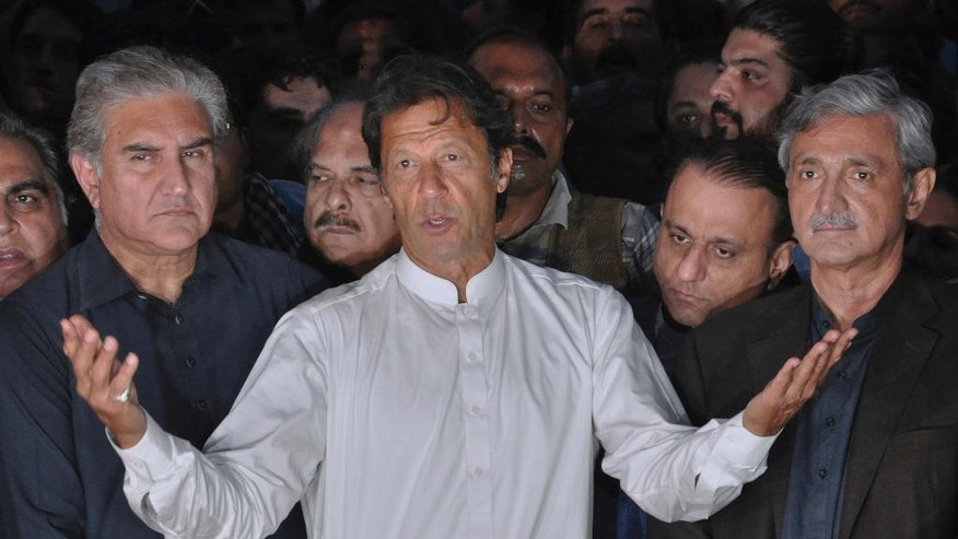 Politician Imran Khan, center, speaks to journalists outside his residence in Islamabad, Pakistan, Sunday, Oct. 30, 2016. Pakistani Interior Minister Chaudary Nisar Ali Khan said at a press conference, Sunday, that the opposition party of of cricketer-turned-politician Imran Khan had plans to storm into Pakistan's secretariat, the main office where all the country's ministries operate from. Imran Khan said Sunday that he didn't have any violent plans. Clashes have been taking place intermittently since Friday when the government imposed a blanket ban on all rallies and protests in the capital. (AP Photo/Anjum Naveed)