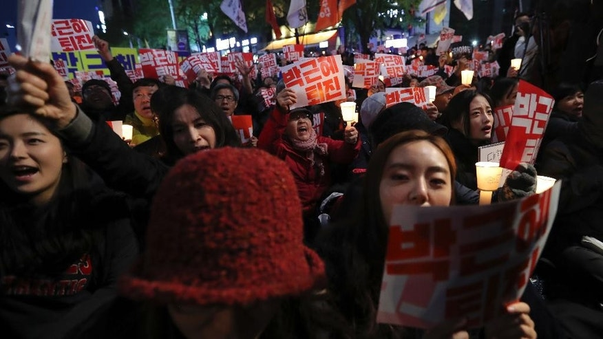 South Koreans shout slogans during an anti-president rally in downtown Seoul, South Korea, Saturday, Oct. 29, 2016. Thousands of South Koreans took to the streets of the capital on Saturday calling for increasingly unpopular President Park Geun-hye to step down over allegations that she let an old friend, the daughter of a religious cult leader, interfere in important state affairs. (AP Photo/Lee Jin-man)