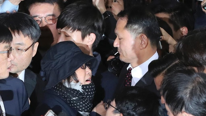 Choi Soon-sil, center left, a cult leader's daughter with a decades-long connection to President Park Geun-hye, is surrounded by prosecutor's officers and media upon her arrival at the Seoul Central District Prosecutors' Office in Seoul, South Korea, Monday, Oct. 31, 2016. South Korea is hoping for answers Monday about its biggest scandal in years. At the center is Choi Soon-sil. Media speculation claims that Choi, who has no official ties to the administration, may have had a major role in government affairs by pulling strings from the shadows while exploiting her relationship with Park for money and favors. (AP Photo/Lee Jin-man)