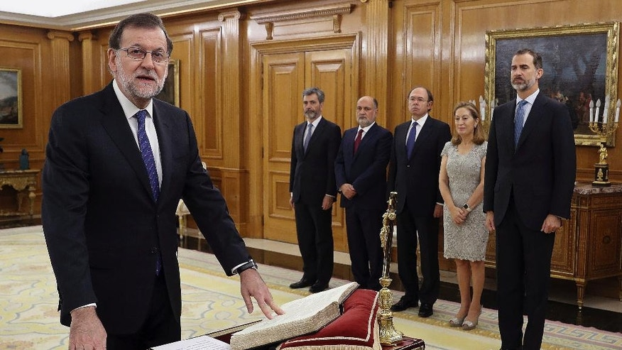 Mariano Rajoy takes the oath as Prime Minister as Spain's King Felipe IV, right, looks on at the Zarzuela Palace in Madrid, Spain Monday Oct. 31, 2016. Spain's Parliament voted to approve acting Prime Minister Mariano Rajoy's bid to form a new minority government last Saturday putting an end to the country's 10-month political deadlock. (Angel Díaz/Pool Photo via AP)