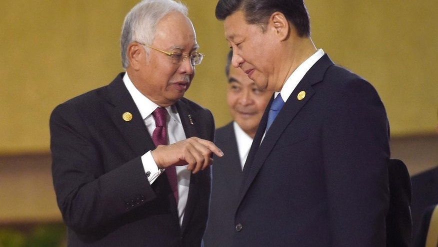 FILE - In this Nov. 19, 2015 file photo, Malaysia's Prime Minister Najib Razak, left, talks with China's President Xi Jinping as they arrive for a family photo with other leaders at the Asia-Pacific Economic Cooperation summit in Manila, Philippines. Following Philippine President Rodrigo Duterte's recent visit to China, Malaysia's prime minister is the latest leader of a state that claims territory in the South China Sea to travel to Beijing. Najib arrives in the Chinese capital on Tuesday, Nov. 1, 2016 for a six-day visit to the country whose claims to virtually the entire strategic waterbody overlaps with areas that Malaysia says belong to it. (AP Photo/Susan Walsh, File)