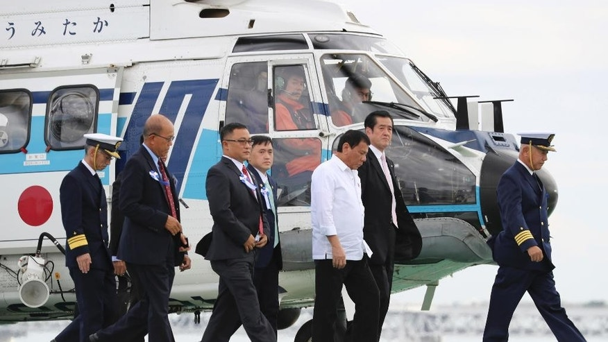 FILE - In this Thursday, Oct. 27, 2016 file photo, Philippine President Rodrigo Duterte, center in white outfit, is escorted on a ship upon his arrival by a helicopter at a Japan Coast Guard base in Yokohama near Tokyo. Duterte proposed joint military exercises with Japan during his visit to Tokyo, while reiterating that he will not conduct them with Americans in his presidency. Duterte made the proposal during his visit to a coast guard unit to observe an exercise from one of the patrol vessels Japan pledged to provide the Philippines to upgrade Manila's maritime security capabilities, largely in response to China's strong assertions of its South China Sea maritime claims. (AP Photo/Eugene Hoshiko, File)