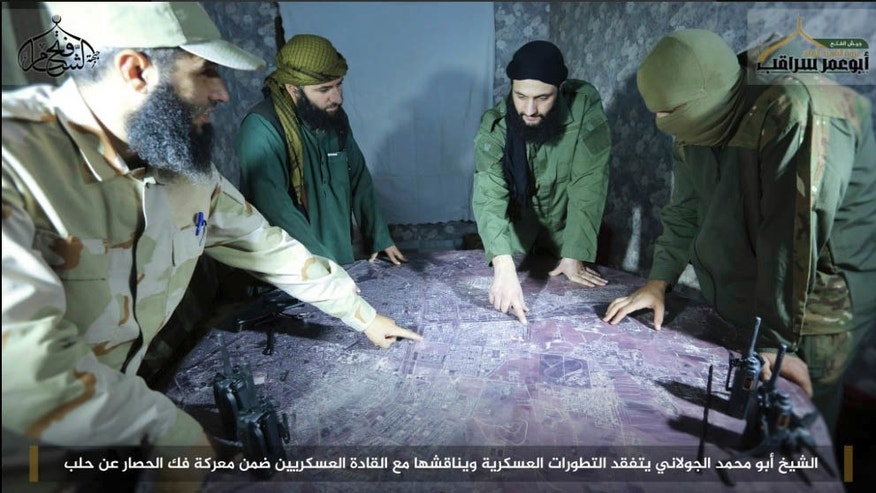 Abu Mohammed al-Golani, the leader of Fatah al-Sham Front, center, is seen in this picture posted by the group, discussing battlefield details with field commanders over a map. An alliance of insurgent groups, known as Army of Conquest and includes al-Qaida-linked Fatah al-Sham Front, said they have advanced into a district in al-Hamadaniyeh, Aleppo, Syria on Sunday, Oct. 30, 2016. Videos posted by the Fatah al-Sham group showed insurgents advancing into the neighborhood in tanks and other military vehicles. Writing in bottom at reads in Arabic: Sheik Abu Mohammed al-Golani inspects military development and discusses them with military commanders as part of the battle for lifting the siege off Aleppo. (Militant UGC via AP)