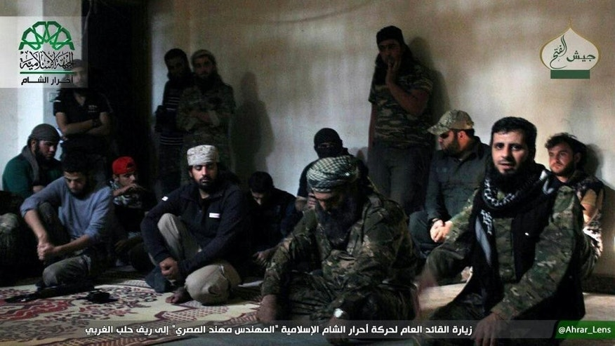 This picture posted, Sunday, Oct. 30, 2016, by the Syrian militant group Ahrar al-Sham, shows the general commander of Ahrar al-sham, Mohannad al-Masri, center, visiting fighters in rural western Aleppo, Syria. An insurgent alliance, known as the Army of Conquest and which includes an al-Qaida-linked group, attacked western Aleppo, aiming to breach a months-long siege on the rebel-held eastern side of the city. (Militant UGC via AP)