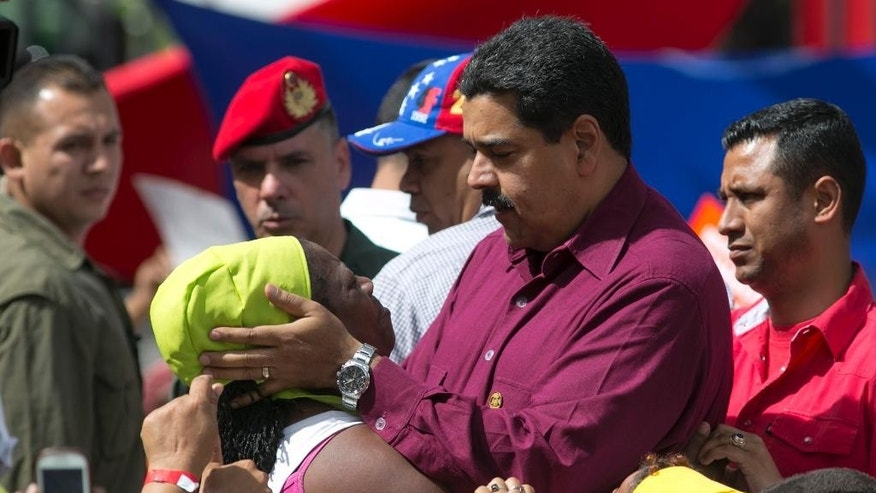 Venezuela's President Nicolas Maduro listens to a supporter during a rally outside Miraflores presidential palace in Caracas, Venezuela, Friday, Oct. 28, 2016. For the most part, residents of Venezuela's capital ignored calls to stay home Friday to protest Maduro, handing a rare victory to the embattled leader. (AP Photo/Ariana Cubillos)