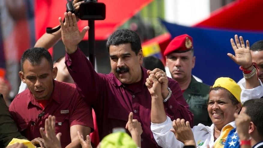Venezuela's President Nicolas Maduro waves to supporters during a rally outside Miraflores presidential palace in Caracas, Venezuela, Friday, Oct. 28, 2016.  For the most part, residents of Venezuela's capital ignored calls to stay home Friday to protest Maduro, handing a rare victory to the embattled leader. (AP Photo/Ariana Cubillos)