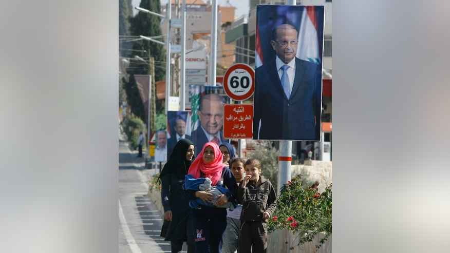 People walk past posters of Christian leader Michel Aoun in the southern port city of Sidon, Lebanon, Sunday, Oct. 30, 2016. Aoun, an 81-year-old veteran politician, is set to be elected by Parliament on Monday as part of a political deal that's expected to be another boost for President Bashar Assad in neighboring Syria. (AP Photo/Mohammed Zaatari)