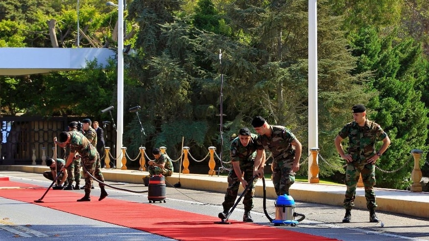 Lebanese soldiers clean a red carpet ahead of the arrival by Christian leader Michel Aoun, the assumed president elect, at the Presidential Palace in Baabda, east of Beirut, Lebanon, Monday, Oct. 31, 2016. Aoun, a former army commander and strong ally of the militant Hezbollah group, is widely expected to win a two-third majority vote to become Lebanon's 13th president at Monday's session of Parliament. (AP Photo/Bilal Hussein)