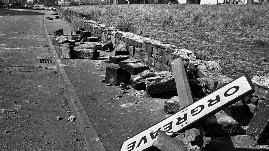 FILE - This June 18, 1984 file photo shows a fallen signpost, felled concrete posts and a broken wall in Orgreave, north east England. Britain's Home Secretary Amber Rudd rejected Monday Oct. 31, 2016, on having an inquiry or independent review into violence between police and miners at Orgreave, one of the fiercest clashes during the 1984-1985 miners' strike. (PA via AP, File)