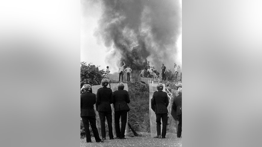 FILE - In this June 18, 1984 file photo, riot police watching as pickets face them against a background of burning cars during the miners strike at the Orgreave coke works in Orgreave, north east England. Britain's Home Secretary Amber Rudd rejected Monday Oct. 31, 2016, on having an inquiry or independent review into violence between police and miners at Orgreave, one of the fiercest clashes during the 1984-1985 miners' strike. (PA via AP, File)