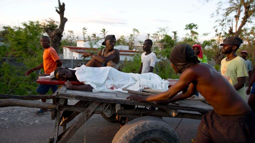 Protesters carry the body of a young teenager on a cart after he was shot amid protests over delays in aid distribution after a Category 4 hurricane pummeled the  Caribbean country last month, in Les Cayes, Haiti. Tuesday Nov. 1, 2016. Mayor Jean Gabriel Fortune said the boy was killed as police clashed with protesters when they tried to climb aboard a boat that had arrived from Puerto Rico carrying supplies. ( AP Photo/Dieu Nalio Chery)