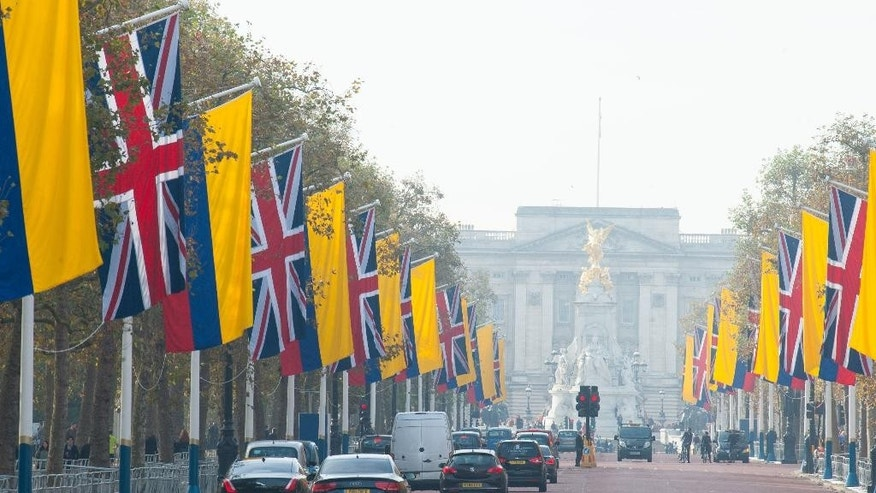 Flags of Britain and Colombia are flown on the Mall, London,  Monday Oct. 31, 2016, the day before the state visit of the Colombian President Juan Manuel Santos. Buckingham Palace is seen in the background. (Dominic Lipinski/PA via AP)