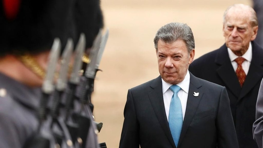Colombia's President Juan Manuel Santos inspects an honour guard with Britain's Prince Philip, behind right, during a ceremonial welcome at Horse Guards Parade in central London, Tuesday Nov. 1, 2016.  The President of Colombia Juan Manuel Santos, this year's Nobel Peace Prize laureate, and his wife, Maria Clemencia Rodriguezis are on a three day state visit to Britain. (Stefan Wermuth/Pool via AP)