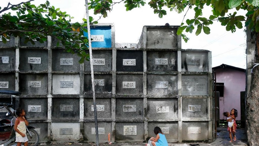 In this Wednesday, Oct. 26, 2016 photo, children play by apartment-type crypts as the country prepares for the traditional honoring of the departed every Nov. 1 known as All Saints Day, at Masantol township, Pampanga province north of Manila, Philippines. On All Saints Day in the country, the cemetery takes center stage - and not at all in the way Halloween does it. This is a time for remembrance and, for many, a time for contemplation. (AP Photo/Bullit Marquez, File)