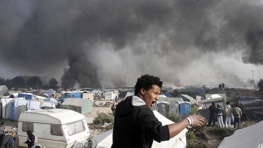 "FILE - In this Wednesday, Oct. 26, 2016 file photo a migrant reacts as smoke billows from burning shelters set on fire in the makeshift migrant camp known as ""the jungle"" near Calais, northern France. (AP Photo/Thibault Camus, File)"