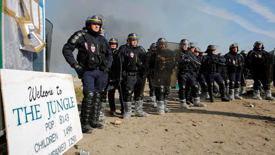 """FILE - In this Wednesday, Oct. 26, 2016 file photo police officers form a line to push back people after fires were started in the makeshift migrant camp known as """"the jungle"""" near Calais, northern France. Firefighters have doused several dozen fires set by migrants as they left the makeshift camp where they have been living near the northern French city of Calais. (AP Photo/Emilio Morenatti, File)"""