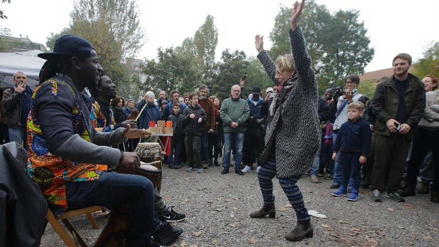 A woman dances as migrants play bongos outside the Montello barracks, in Milan, Italy, Tuesday, Nov. 1, 2016. More than a thousand Italians turned out to welcome a group of migrants who have been moved to a recently purposed military barracks following demonstrations against their presence. (AP Photo/Luca Bruno)