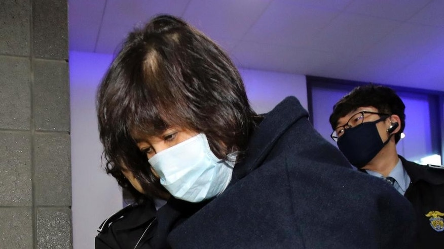 "Choi Soon-sil, a woman at the center of a scandal that threatens the country's president, arrives for questioning at the Seoul Central District Prosecutors Office in Seoul, South Korea, Tuesday, Nov. 1, 2016. South Korean police detained a man who rammed a large excavator into a gate Tuesday near the office where prosecutors questioned Choi. The woman had earlier said she ""deserves death"" and the detained man said he ""came here to help her die."" (Kim Do-hun/Yonhap via AP)"