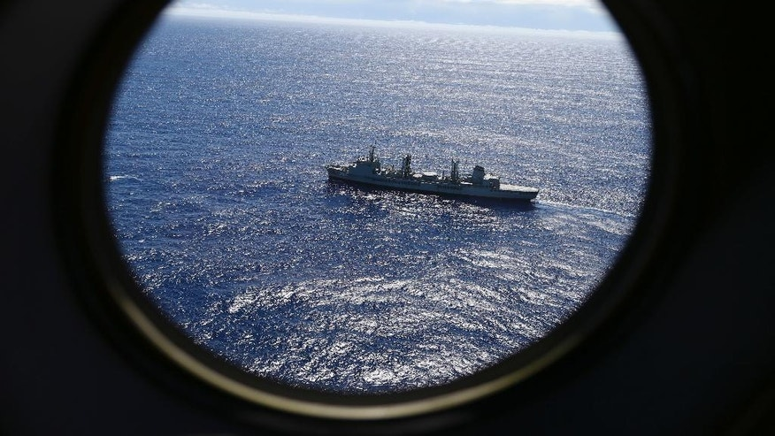FILE - In this March 31, 2014 file photo, HMAS Success scans the southern Indian Ocean, near the coast of Western Australia, as a Royal New Zealand Air Force P3 Orion flies over, while searching for missing Malaysia Airlines Flight MH370. A fresh analysis of the final moments of doomed Malaysia Airlines Flight 370, released by the Australian Transport Safety Bureau Wednesday, Nov. 2, 2016, suggests no one was controlling the plane when it plane plunged into the ocean. (AP Photo/Rob Griffith, File)