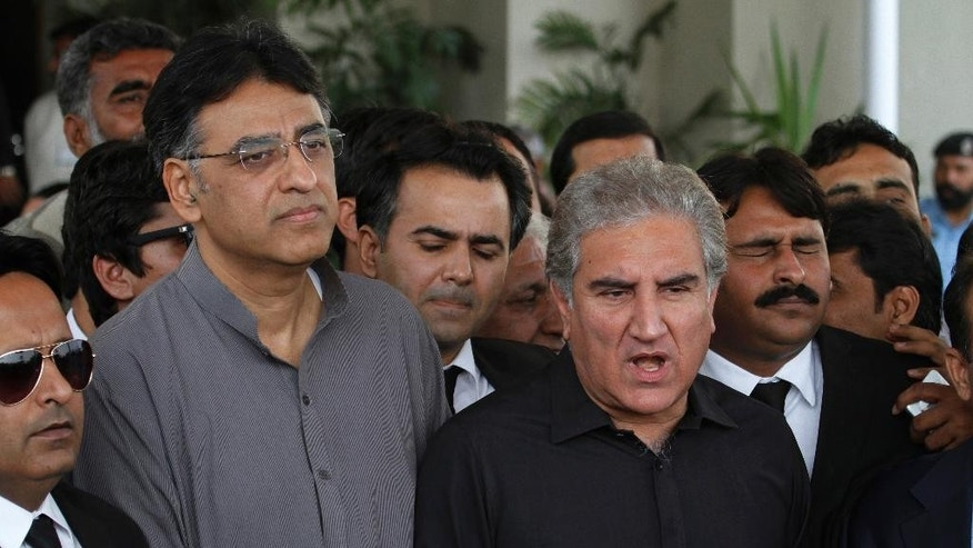 Shah Mahmood Qureshi, center right, a leader in the opposition Pakistan Tehreek-e-Insaf party, is surrounded by lawyers and his party colleagues as he speaks to journalists outside the Supreme Court, in Islamabad, Pakistan, Tuesday, Nov. 1, 2016. Pakistan's Supreme Court on Tuesday adjourned the hearing of the Panama Papers case seeking disqualification of Pakistani Prime Minister Nawaz Sharif over a financial scandal involving his family. One of the petitions came from the opposition party of cricketer turned politician Imran khan who is threatening to bring tens of thousands of protesters to the capital on Nov. 2 to press for Sharif's disqualification. (AP Photo/Anjum Naveed)