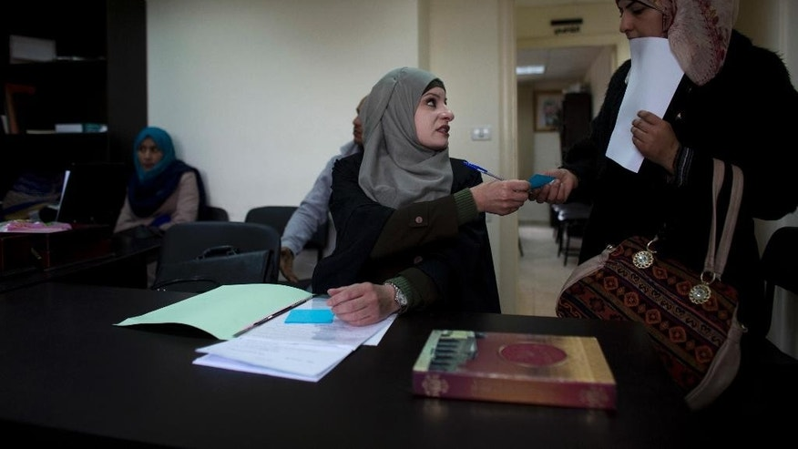 In this Tuesday, March 29, 2016 photo, Palestinian divorce lawyer Reema Shamashneh talks to her client in the Islamic family court in Ramallah, West Bank.  One divorce at a time, the Palestinian lawyer fights for female clients in an Islamic family court where a man's testimony is worth twice a woman's. Shamasneh, a devout Muslim, believes the laws are the way they are because they were passed by men. She shuns traditional marriage for herself, saying she can take care of herself.(AP Photo/Dusan Vranic)