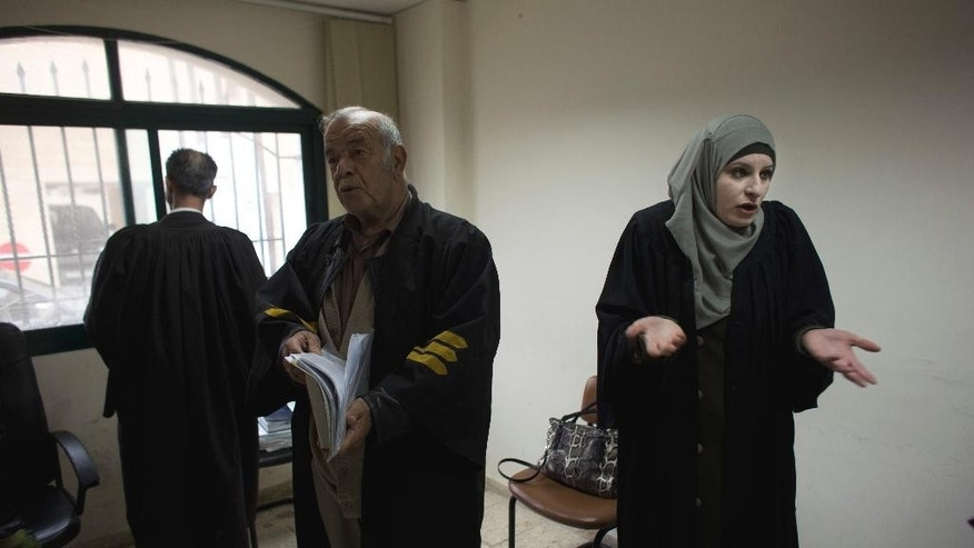 In this Tuesday, March 29, 2016 photo, Palestinian divorce lawyer Reema Shamashneh, right, speaks with her colleagues during a break at the Islamic family court in Ramallah, West Bank. One divorce at a time, the Palestinian lawyer fights for female clients in an Islamic family court where a man's testimony is worth twice a woman's. Shamasneh, a devout Muslim, believes the laws are the way they are because they were passed by men. She shuns traditional marriage for herself, saying she can take care of herself. (AP Photo/Dusan Vranic)