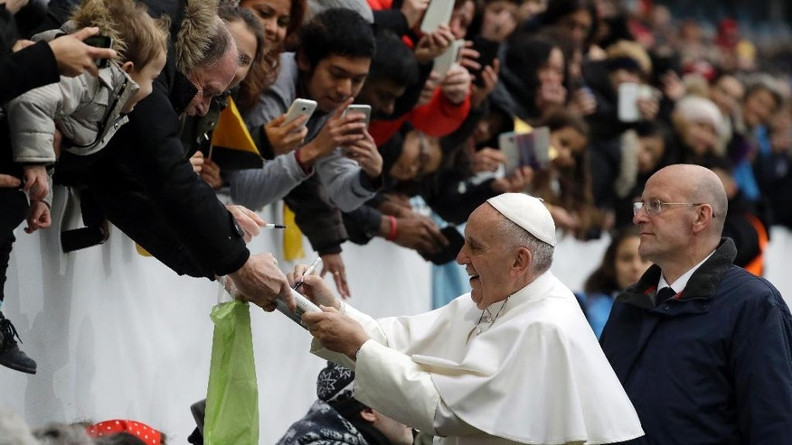 """Pope Francis signs a book as he greets faithful upon his arrival at the Malmo stadium, Sweden, Tuesday, Nov. 1, 2016. Francis traveled to secular Sweden on Monday to mark the 500th anniversary of the Protestant Reformation, a remarkably bold gesture given his very own Jesuit religious order was founded to defend the faith against Martin Luther's """"heretical"""" reforms five centuries ago. (AP Photo/Andrew Medichini)"""