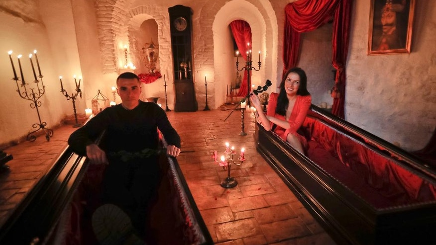 Tami Varma and her brother Robin, the grandchildren of Devendra Varma, a scholar of English gothic tales and an expert in vampire lore, pose in coffins at Bran Castle, in Bran, Romania, Monday, Oct. 31, 2016. A Canadian brother and sister are passing Halloween night curled up in red velvet coffins in the Transylvanian castle that inspired the Dracula legend, the first time in 70 years anyone has spent the night in the gothic fortress after they bested 88,000 people who entered a competition hosted by Airbnb to get the chance to dine and sleep at the castle in Romania. (AP Photo/Vadim Ghirda)
