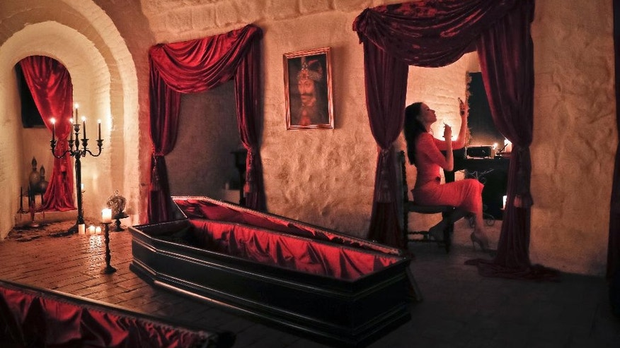 Tami Varma, granddaughter of Devendra Varma, a scholar of English gothic tales and an expert in vampire lore, adjusts her makeup at the Bran Castle, in Bran, Romania, Monday, Oct. 31, 2016. A Canadian brother and sister are passing Halloween night curled up in red velvet coffins in the Transylvanian castle that inspired the Dracula legend, the first time in 70 years anyone has spent the night in the gothic fortress, after they bested 88,000 people who entered a competition hosted by Airbnb to get the chance to dine and sleep at the castle in Romania. A portrait of medieval prince Vlad the Impaler is placed on the wall. (AP Photo/Vadim Ghirda)