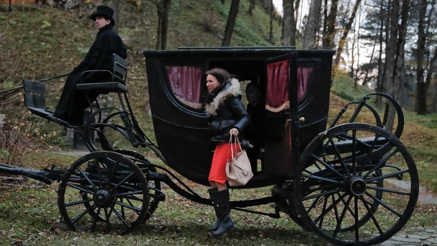 Tami Varma jumps out of the stagecoach that brought her and her brother Robin, the grandchildren of Devendra Varma, a scholar of English gothic tales and an expert in vampire lore, at the Bran Castle, in Bran, Romania, Monday, Oct. 31, 2016. A Canadian brother and sister are passing Halloween night curled up in red velvet coffins in the Transylvanian castle that inspired the Dracula legend, the first time in 70 years anyone has spent the night in the gothic fortress, after they bested 88,000 people who entered a competition hosted by Airbnb to get the chance to dine and sleep at the castle in Romania. (AP Photo/Vadim Ghirda)