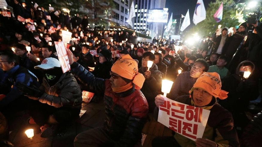 "South Korean protesters stage a rally calling for President Park Geun-hye to step down in downtown Seoul, South Korea, Tuesday, Nov. 1, 2016. South Korean police detained a man who rammed a large excavator into a gate Tuesday near the office where prosecutors questioned a woman at the center of a scandal that threatens the country's president. The woman had earlier said she ""deserves death"" and the detained man said he ""came here to help her die."" The letters read ""Park Geun-hye should step down."" (AP Photo/Ahn Young-joon)"
