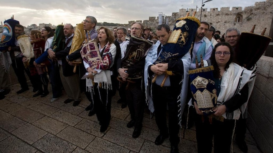 The heads of the Jewish Reform and Conservative movements carry Torah scrolls as they march to the Western Wall, the holiest site where Jews can pray in Jerusalem's Old City, Wednesday, Nov. 2, 2016. Leaders of liberal Jewish movements in the U.S. and Israel have demonstrated for equal prayer at a Jewish holy site, despite a plea from Israel's prime minister not to push the matter publicly. (AP Photo/Sebastian Scheiner)