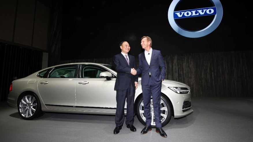 """Li Shufu, Chairman of Zhejiang Geely Holdings, left, shakes hands with Hakan Samuelsson, CEO of Volvo Cars, right, in front of a new S90 Volvo car in Shanghai, China, Wednesday, Nov. 2, 2016. Volvo Cars and its Chinese owner are revving up their profile as they focus on selling premium cars in world markets. The companies announced a strategy Wednesday that includes a new factory to make vehicles based on a new shared platform, including vehicles for Geely's new """"connected car"""" brand, Lynk & Co. (AP Photo)"""