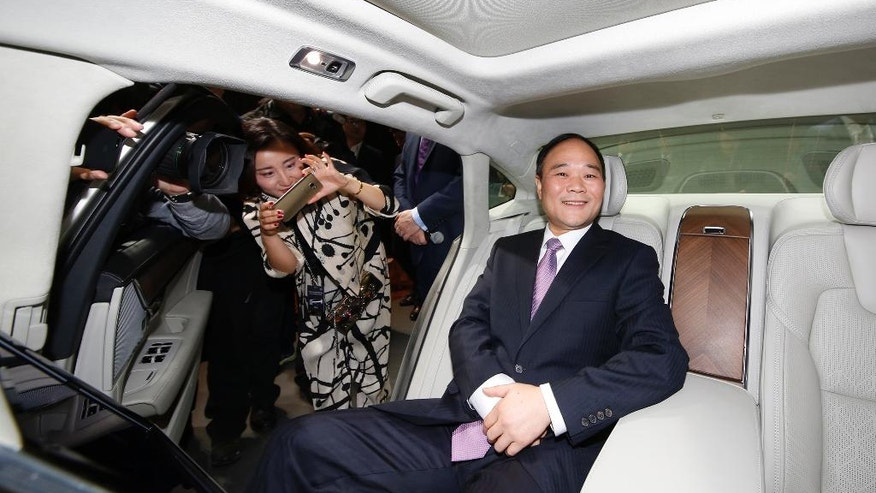 """Li Shufu, Chairman of Zhejiang Geely Holdings, poses for photos in a new S90 Volvo car in Shanghai, China, Wednesday, Nov. 2, 2016. Volvo Cars and its Chinese owner are revving up their profile as they focus on selling premium cars in world markets. The companies announced a strategy Wednesday that includes a new factory to make vehicles based on a new shared platform, including vehicles for Geely's new """"connected car"""" brand, Lynk & Co. (AP Photo)"""