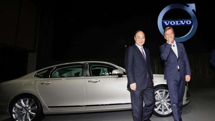 "Li Shufu, Chairman of Zhejiang Geely Holdings, left, and Hakan Samuelsson, CEO of Volvo Cars, right, walk in front of a new S90 Volvo car in Shanghai, China Wednesday Nov. 2, 2016. Volvo Cars and its Chinese owner are revving up their profile as they focus on selling premium cars in world markets. The companies announced a strategy Wednesday that includes a new factory to make vehicles based on a new shared platform, including vehicles for Geely's new ""connected car"" brand, Lynk & Co. (AP Photo)"
