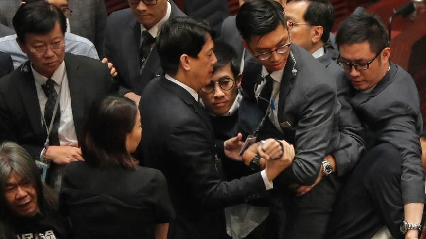 Newly elected Hong Kong lawmaker Sixtus Leung, center with glasses, is blocked by security guards wearing gray suits, as he tries to retake oath at legislature council in Hong Kong, Wednesday, Nov. 2, 2016. Two newly elected pro-democracy Hong Kong lawmakers barred for insulting China in their swearing-in ceremony have set off another round of disorder by scuffling with guards as they tried to retake their oaths in the chamber. (AP Photo/Vincent Yu)